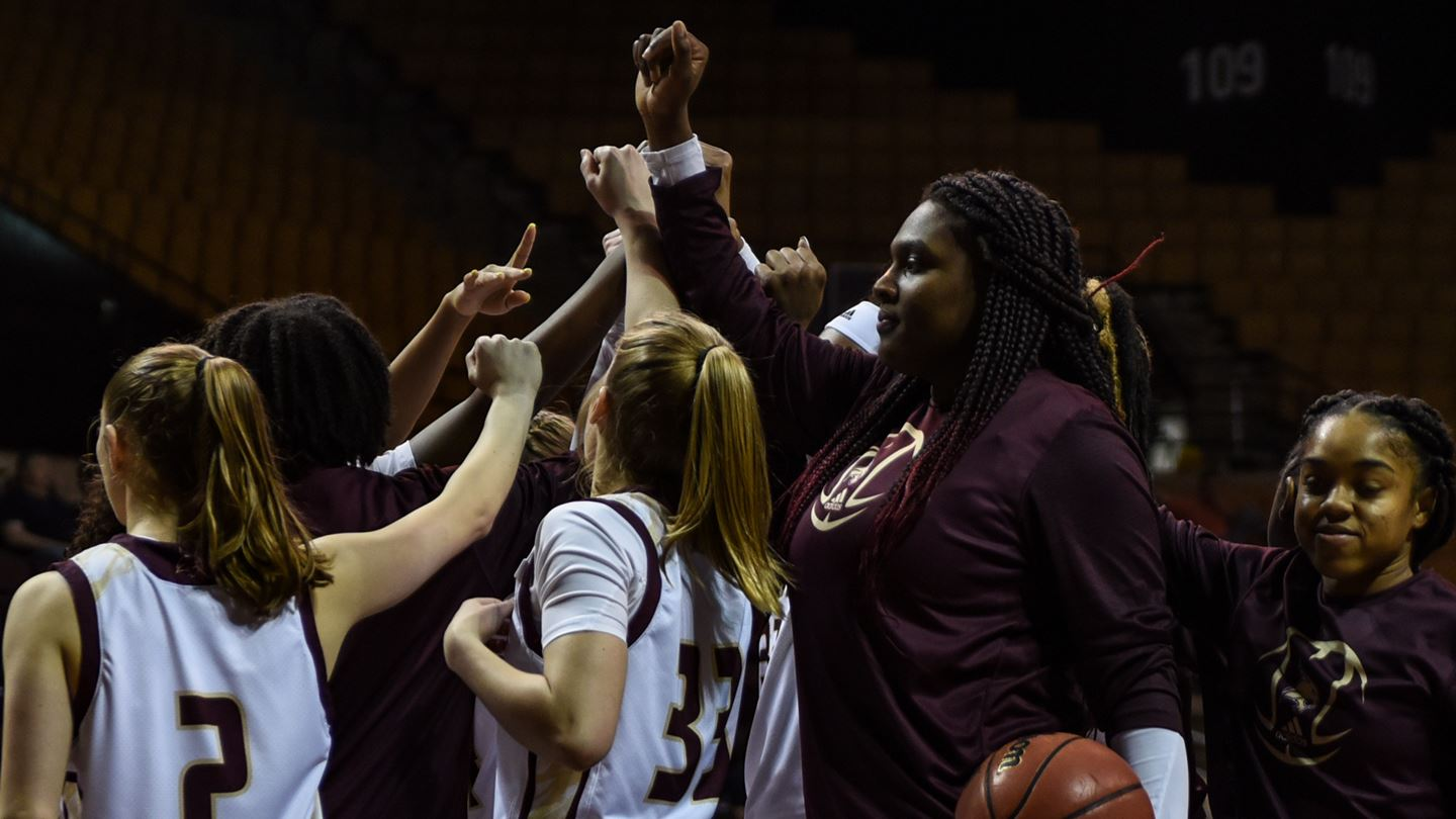 Texas State Women's Basketball stand in a huddle with their hands together in the air.