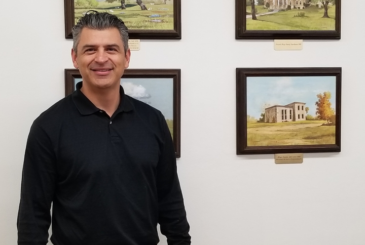Ruben Becerra in a black shirt in front of a wall with paintings of San Marcos.