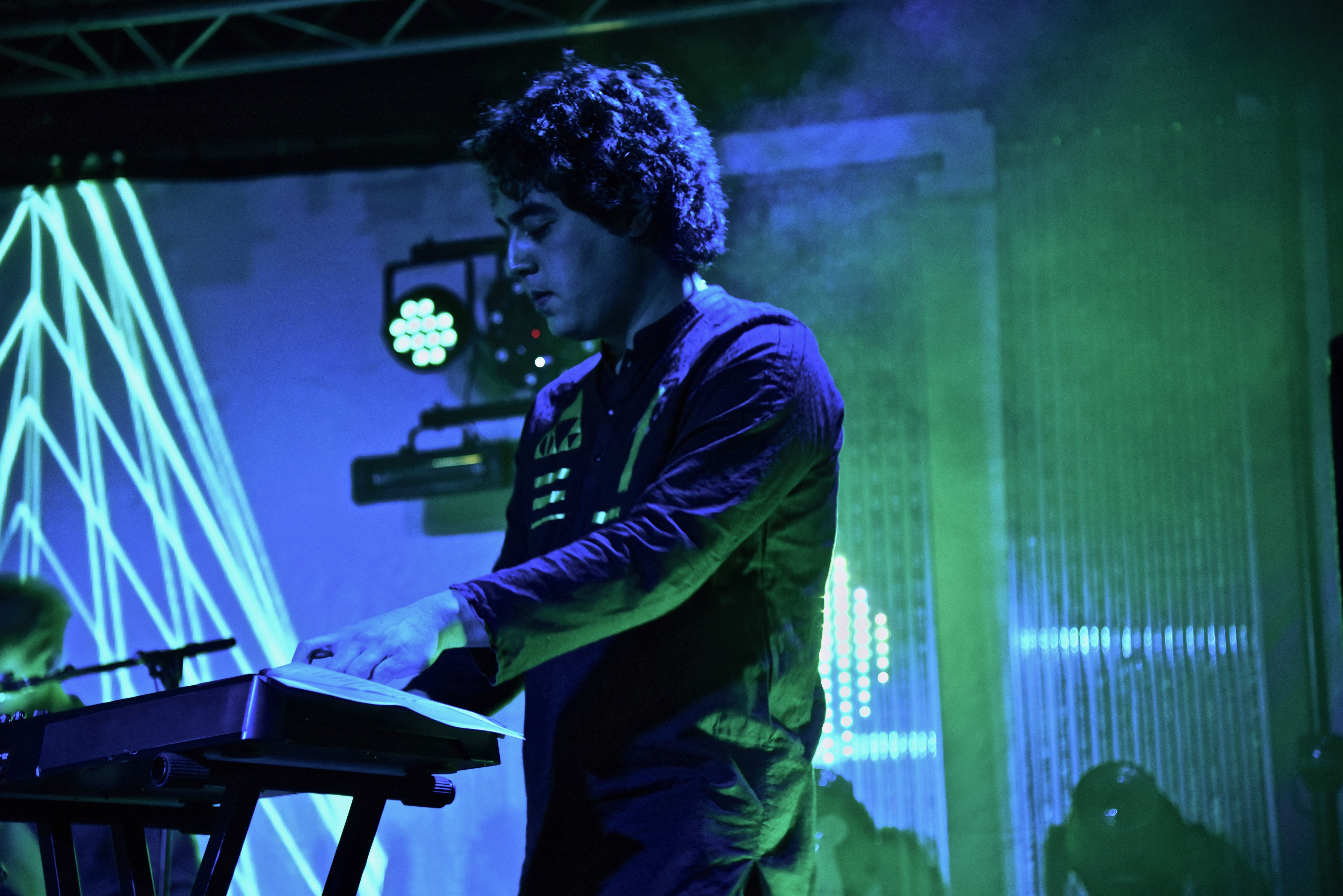 A man with curly hair playing keyboard under blue lights.