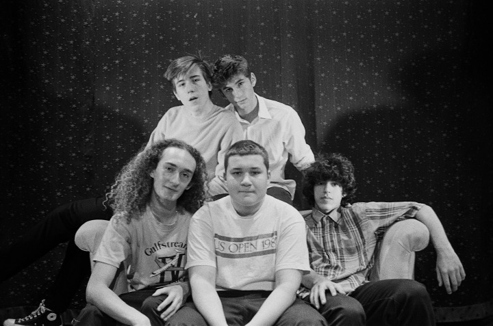 Five teenage boys sitting on and on top of a couch against a dotted background.