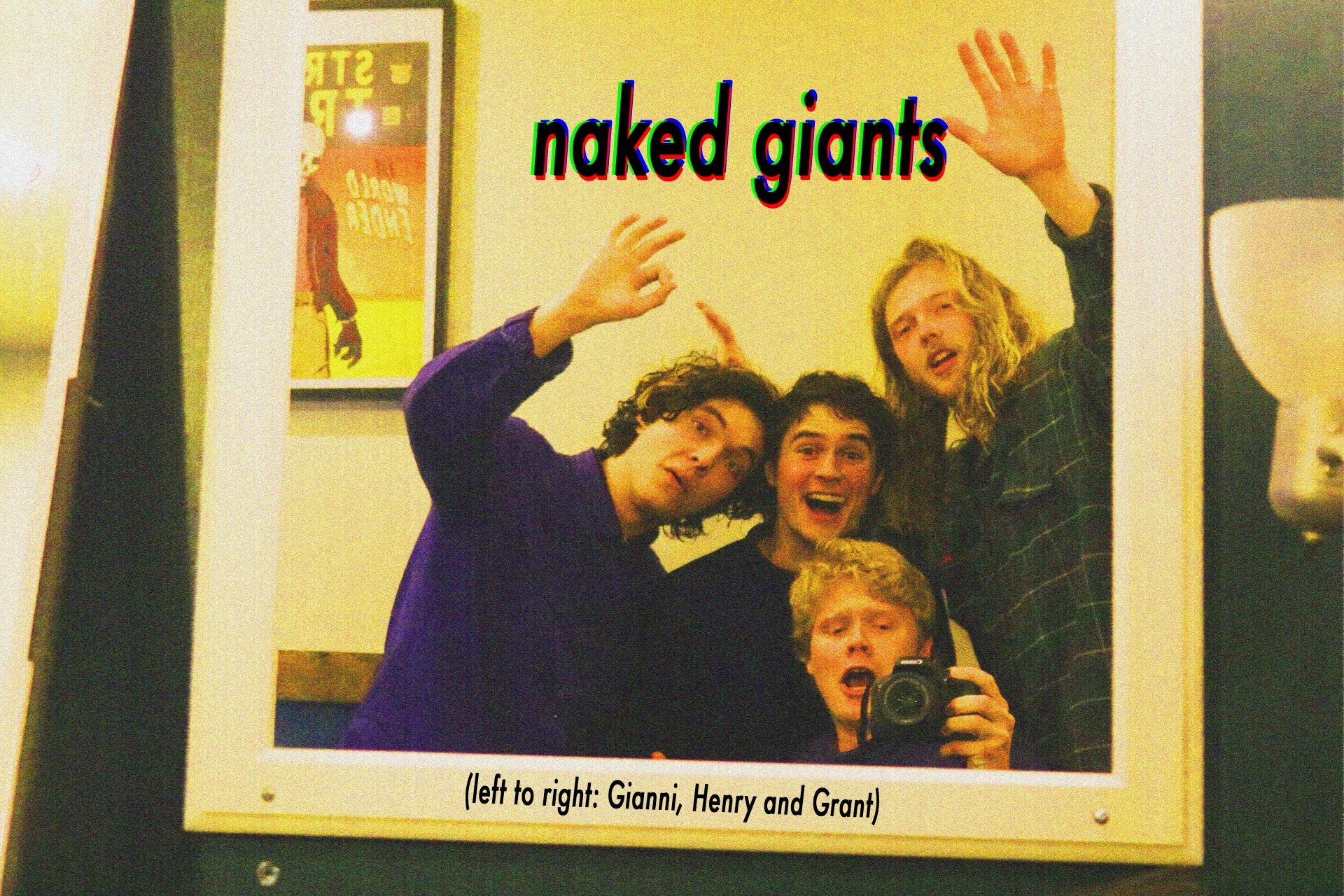 The photo is of the three young male band members for Naked Giants posing in front of a Green Room mirror with a young male journalist taking the photo.