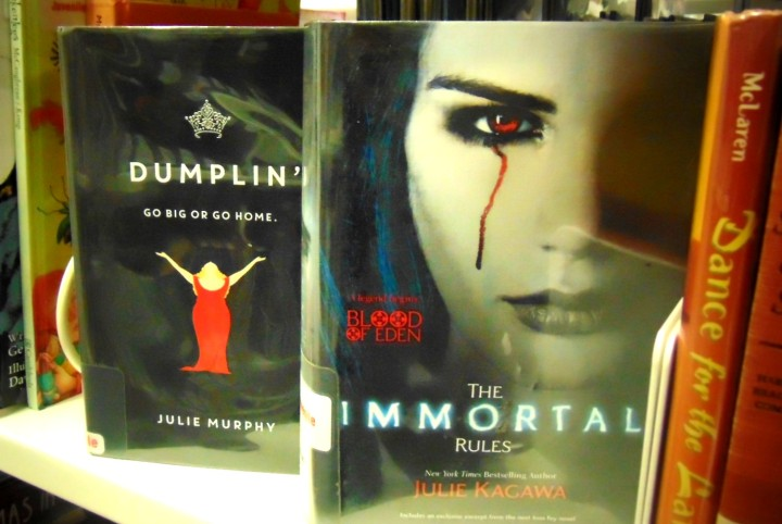 Two books on a shelf, one in front of the other. The book in front is The Immortal Rules from the Blood of Eden series.The cover shows a girl with black hair crying one tear of blood. The book in the back is Dumplin and shows a plus sized girl in a red dress on the cover.