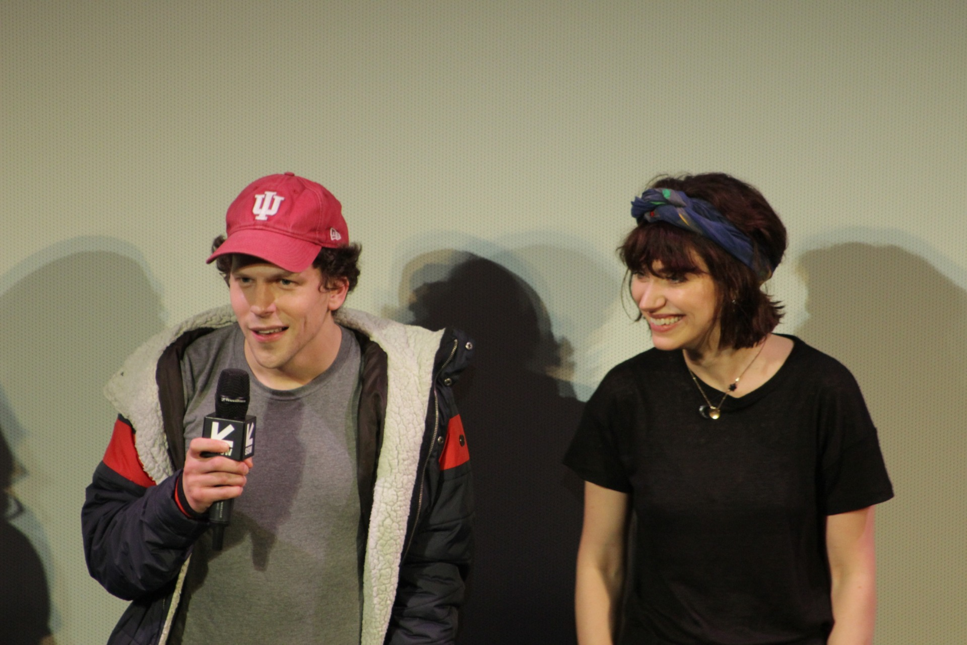 Jesse Eisenburg in a red cap and parka holding a microphone.