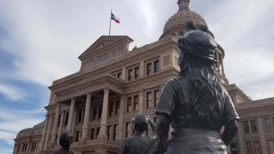 The Texas State Capitol building with statues in front looking up at the building.