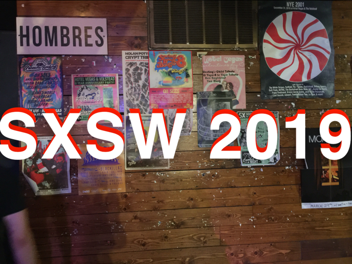 colorful band posters for SXSW 2019 on wall of venue
