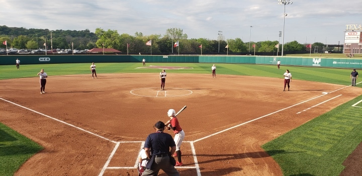 Texas State Softball on defense against Lamar University with several Texas State players on the field in position.