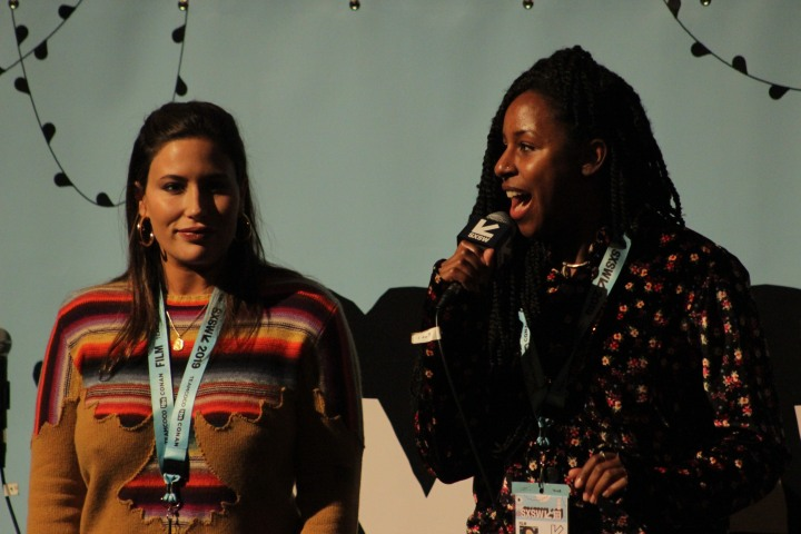Stella Meghie in a floral print shirt and braids holding a microphone.