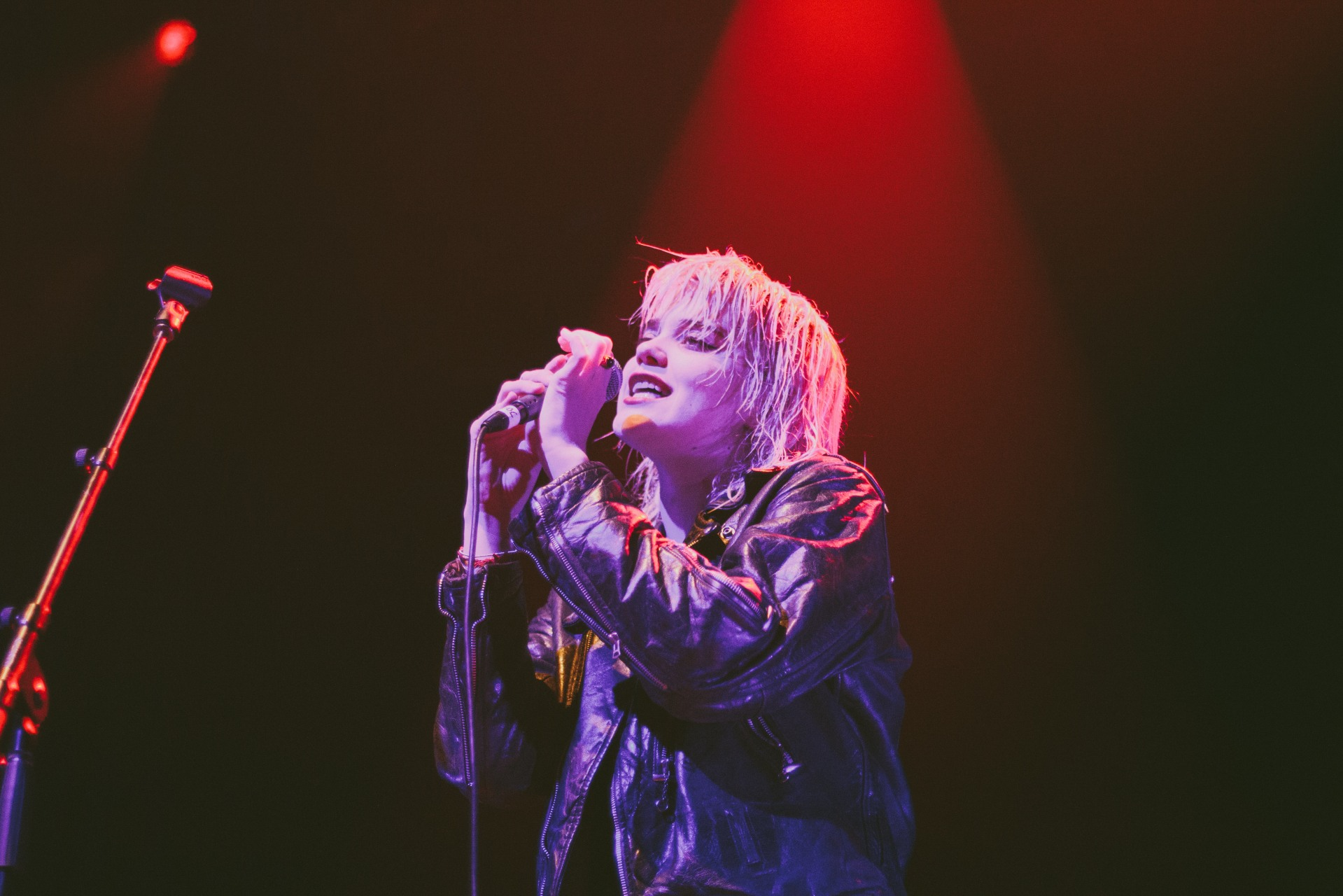 This picture is of a blonde Sky Ferreira singing into a mircrophone with red and blue lights in the background.
