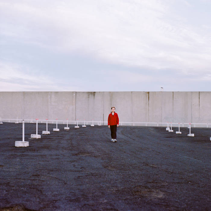 The photo is of Darvid Thor standing in front of a cement wall. Thor is wearing a red half zip jacket, black pants and white sneakers.