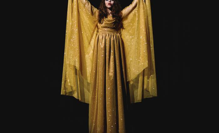 Claire Morales standing in yellow dress with arms stretched upwards