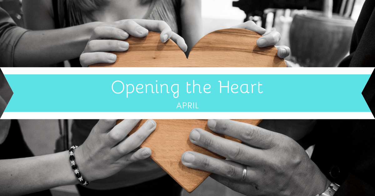 """Three sets of hands holding a wooden heart. Across the heart is a banner that says """"Opening the Heart"""" and """"April."""""""