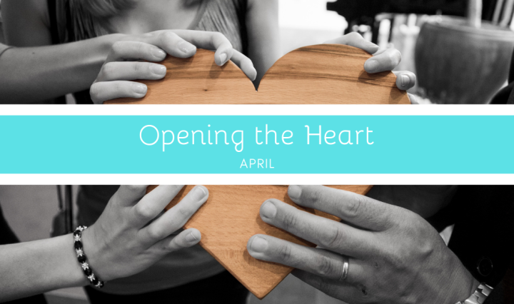 "Three sets of hands holding a wooden heart. Across the heart is a banner that says ""Opening the Heart"" and ""April."""
