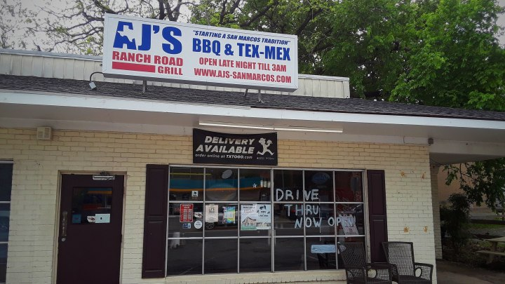 "The restaurant presides in a cream colored brick building with a sign over the entrance door that says "" AJ's Ranch Road Grill BBQ & Tex-Mex"" in huge blue bolded letters."