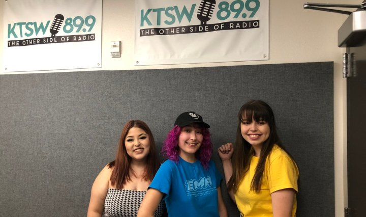 Three girls pose on front of KTSW banner.