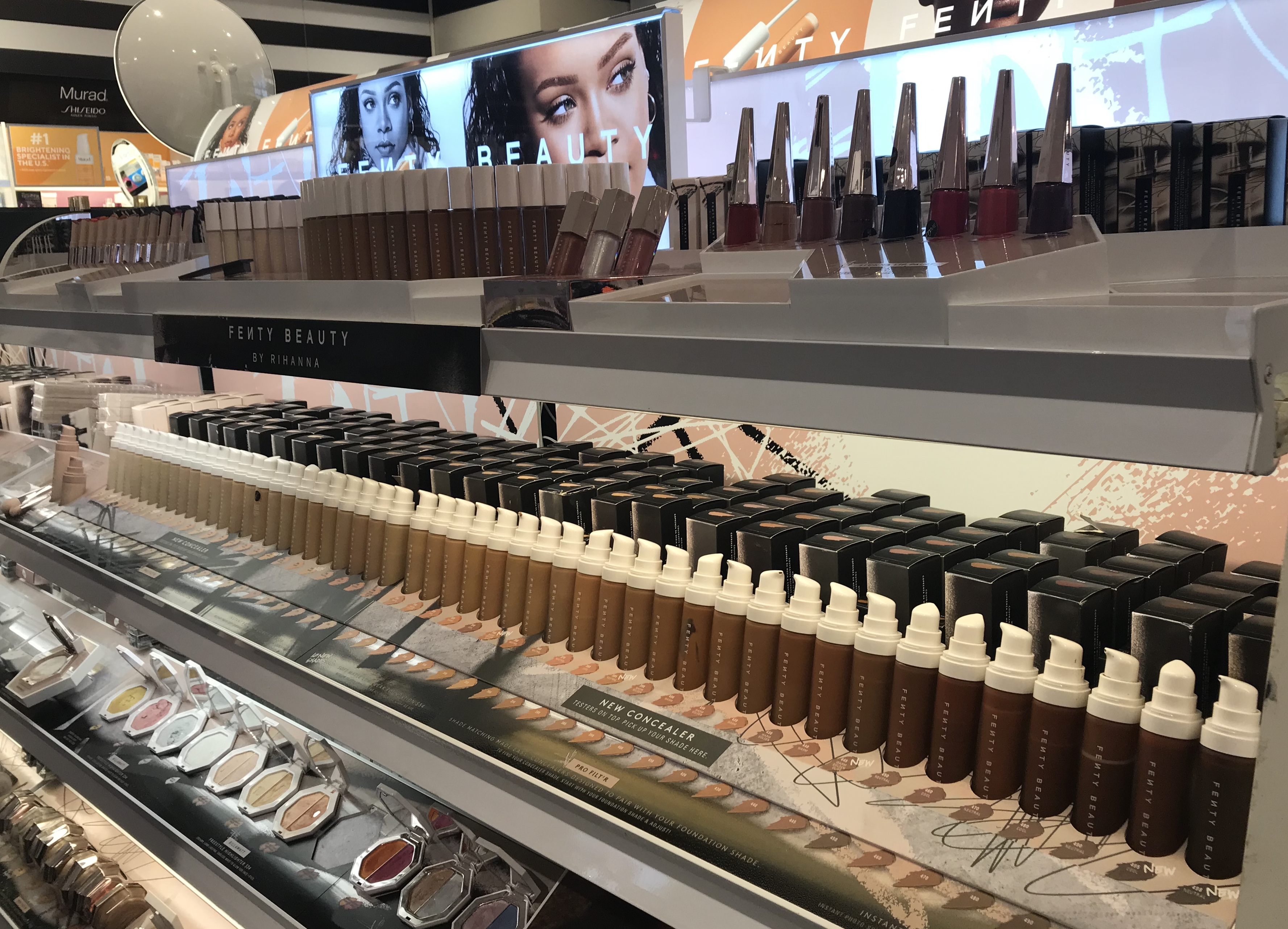A white makeup rack of Fenty Beauty carrying 50 shades of concealer on the top row, 50 shades of foundation on the middle row, and 11 shimmering highlighters on the bottom row