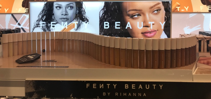 Fifty different shades of concealer in front of the white lettering and two pictures of Rihanna and Fenty Beauty