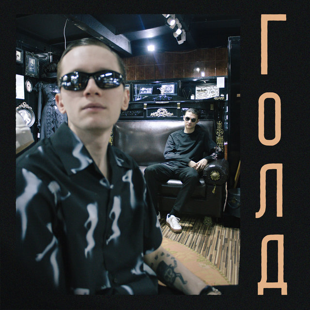 The left side of the album cover shows a man with sunglasses sitting in front of another man with sunglasses, as they both stare off to the side