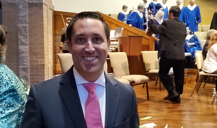Glenn Hegar stands in front of the church altar. Several Choir members in robes can be seen in the background as well as other church attendees.