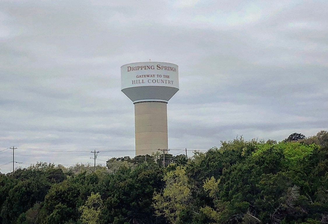 The Dripping Springs water tower surrounded by cloudy skies and green trees.