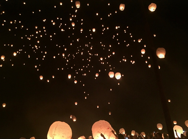 People crowd as they release paper lanterns into the sky..