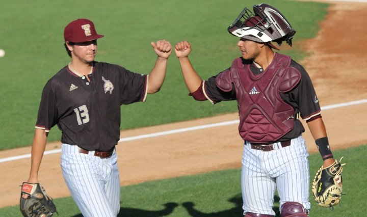 Catcher Felipe Rodriguez and pitcher Brandon Lewis fist-bump near the mound after getting the win.