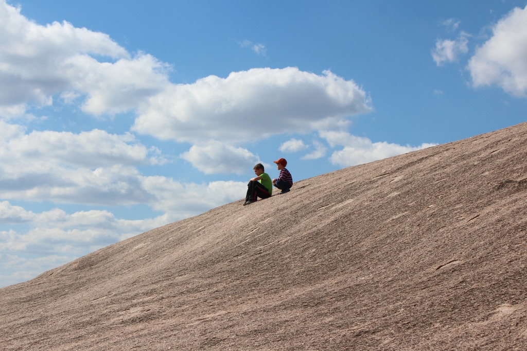 Two young boys sitting on the rock with the blue sky and clouds behind them.