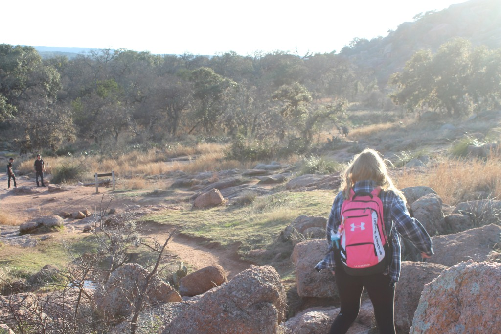 a girl wearing a flannel and a backpack with blonde hair walking amongst rocks as the sun lowers