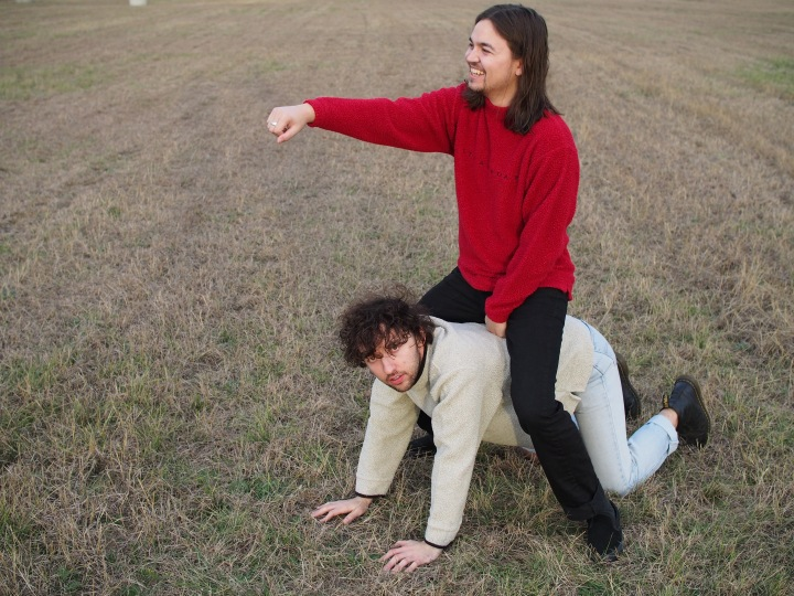 Austin sitting on top of Skyler's back in the middle of a grassy field.