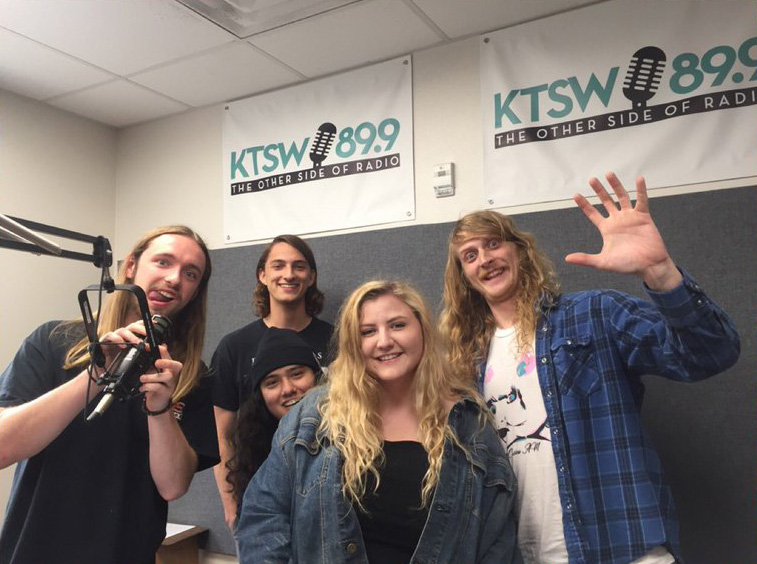 One girl and four boys gathered around a mic in the KTSW studio.