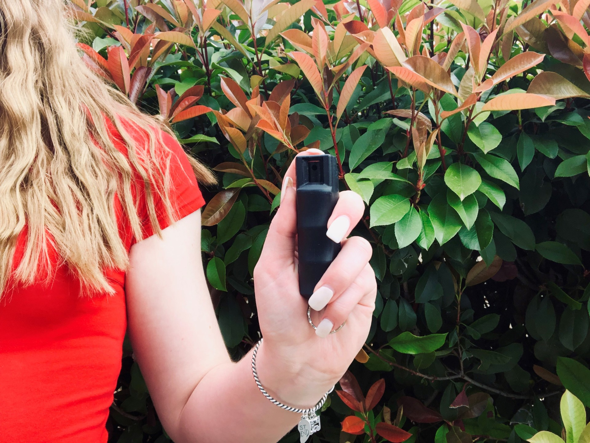 Girl in red holding pepper spray in front of a hedge.