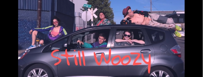 """Still Woozy in a car. His friends are inside and on top of the car. The words """"Still Woozy"""" are placed over the side of the car."""