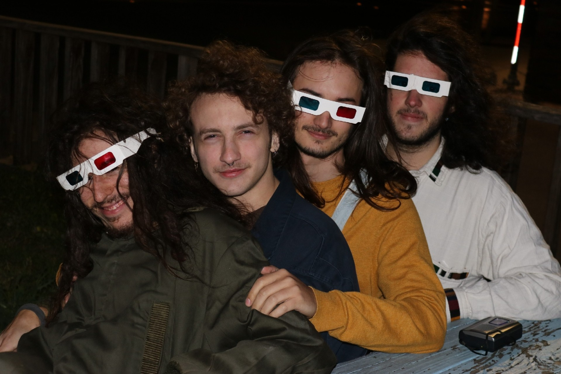Four men sit, back to chest, all but one wearing white 3D movie glasses.