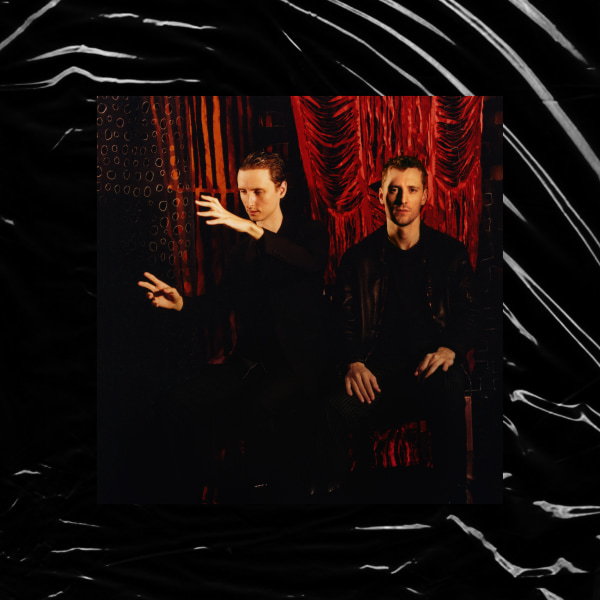 The artwork is a picture of the two brothers in front of a red background wearing all black and one is pretending to play some sort of instrument with his hands