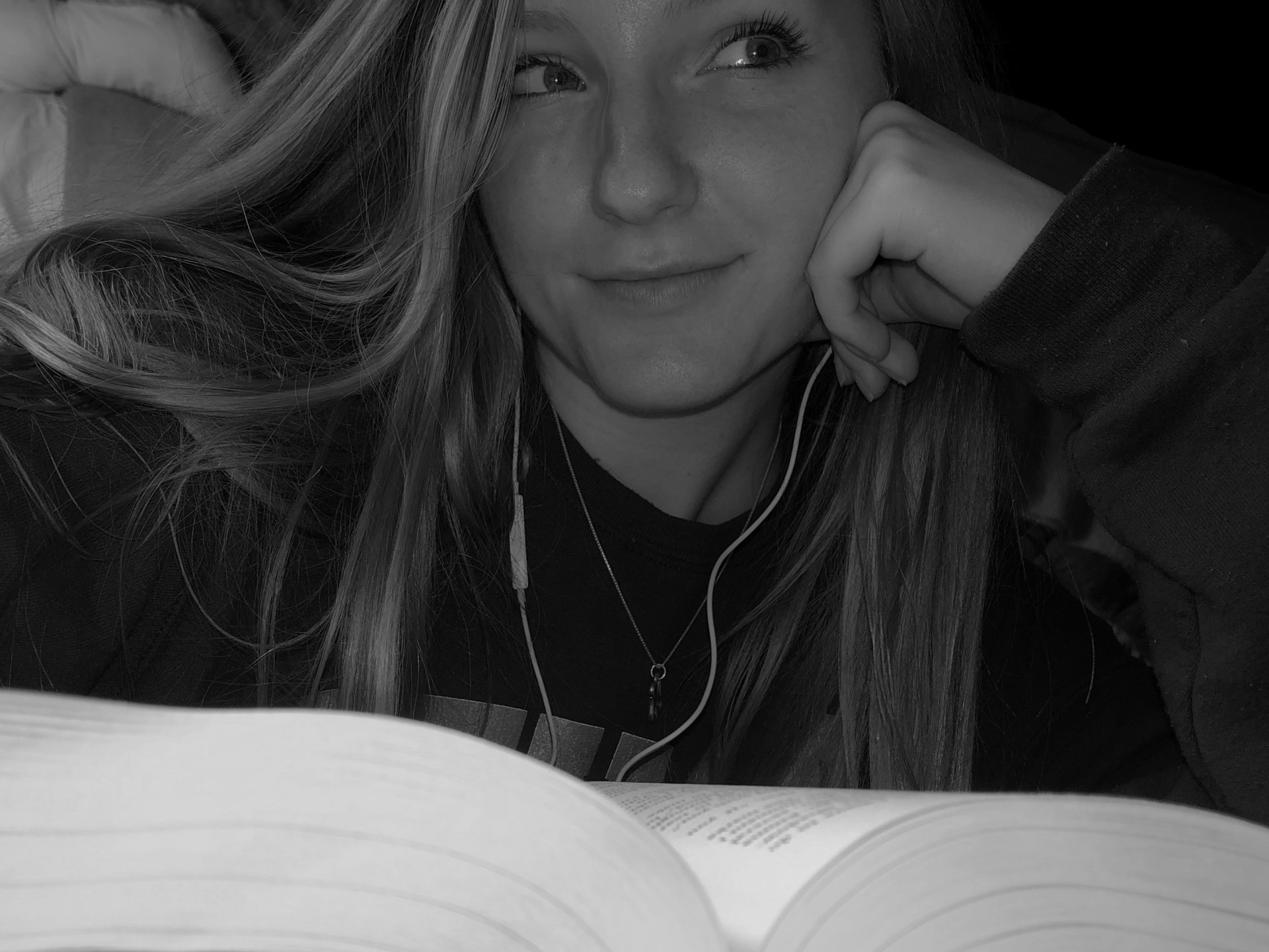 Girl looking off to the side with a book in front of her.
