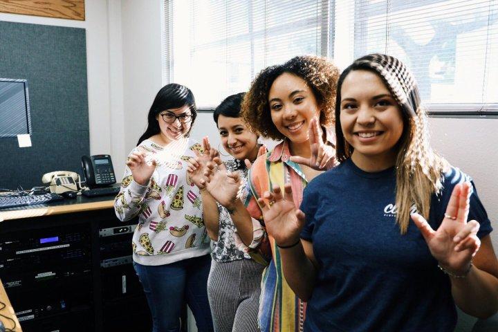 Four girls pose doing bobcat hand sign.