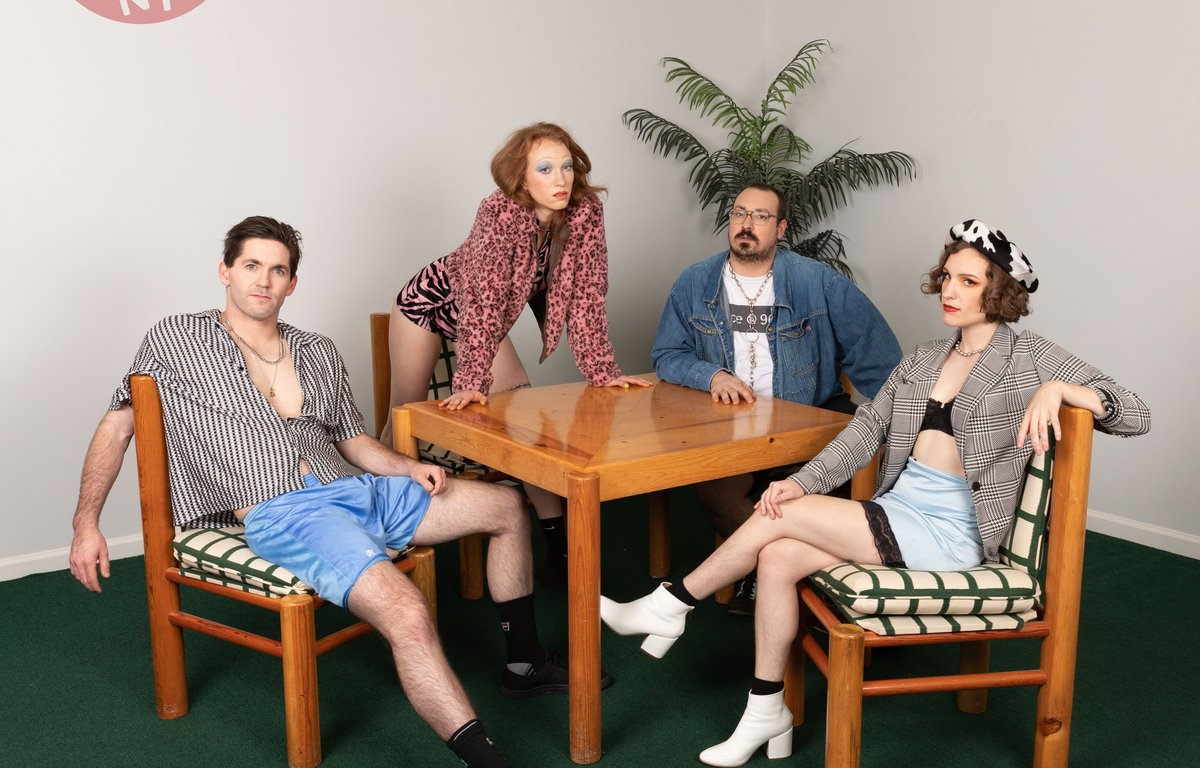 The album cover is four band members dressed in retro clothing, sitting at a table and all facing the camera.