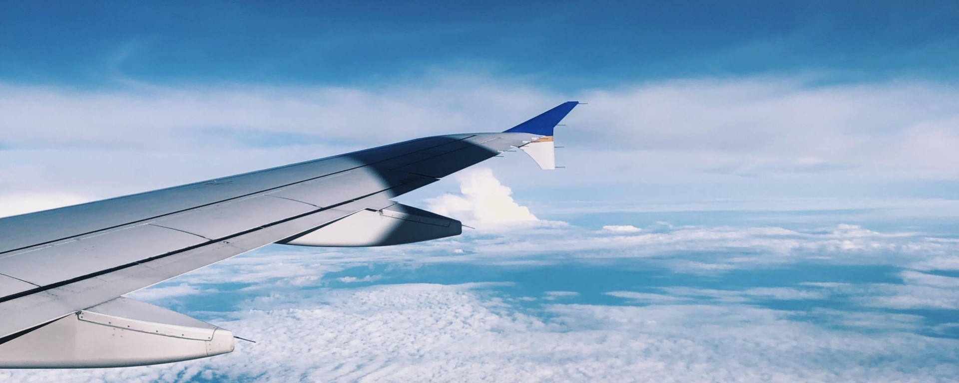 An airplane wing overlooking clouds and the ocean.