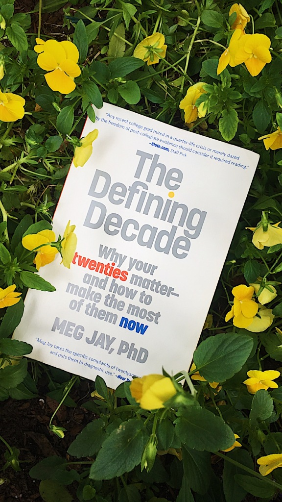 "A copy of ""The Defining Decade"" by Dr. Meg Jay laid on top of yellow flowers."