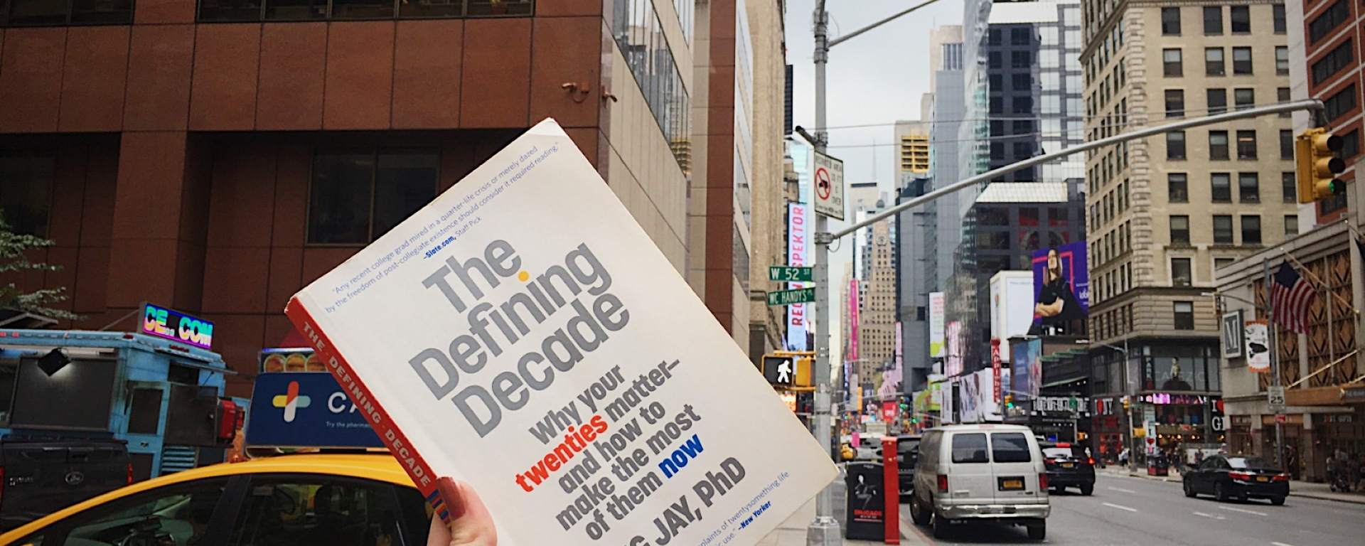 "A copy of ""The Defining Decade"" by Dr. Meg Jay held up from a New York street against Times Square buildings."