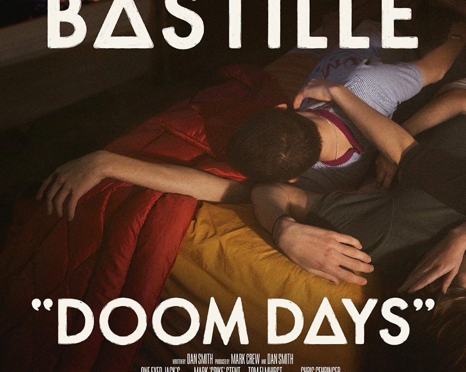 This album cover is a couple of fully-clothed people lying on an unmade bed, with the left-most person looking out of an open window. The text listing the album title and band name is all stylized to make this look like a movie poster.