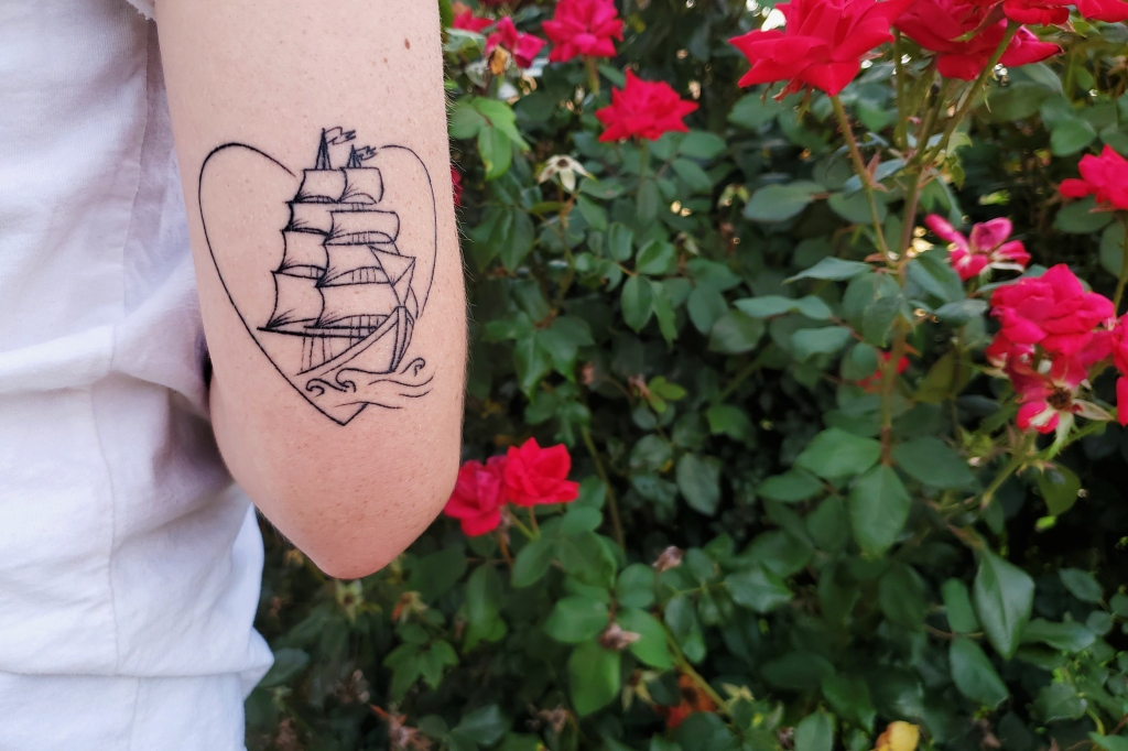 A tattoo on the back of an arm above the elbow of a large ship coming out of a heart.
