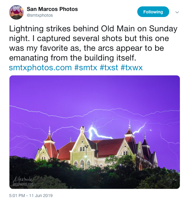 "This image is a tweet by San Marcos Photos. The image tweeted out captures the top of the Old Main building on Texas State University's campus. The rest of the building is hidden under trees. The gold and maroon-roofed building is lit up by the lightning strikes around it. There are multiple horizontal lightning strikes in the sky of all different sizes and intensity of light. The sky is a an indigo-purple color. The text of the tweet which appears above the image says, ""Lightning strikes behind Old Main on Sunday night. I captured several shots but this one was my favorite as, the arcs appear to be emanating from the building itself. smtxphotos.com #smtx #txst #txwx"""