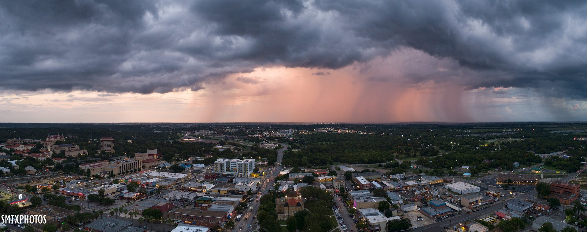 A photo from above of the San Marcos town at sunset. The sky has shades of pink and orange and the clouds in the distance have rain pouring.