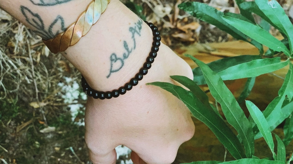 "A tattoo with the words ""Bel Air"" written in cursive on the top of a forearm. The arm has a black beaded bracelet and a gold bracelet and there are grass and leaves in the background."