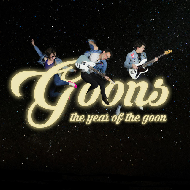 "The word ""Goons"" is displayed in big, cursive letters in the center of the image over a black, star filled background. ""The Year of the Goon"" is spelled out in all lowercase letters to the bottom right of the band name. All three members of the band are jumping over the name wearing denim jackets and holding their instruments."