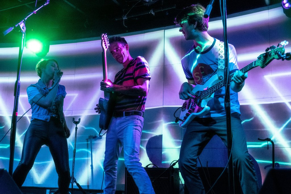 All three members of Goons performing on a low-lit stage in Austin, Texas. There are colorful projections of beams and lasers in the background.