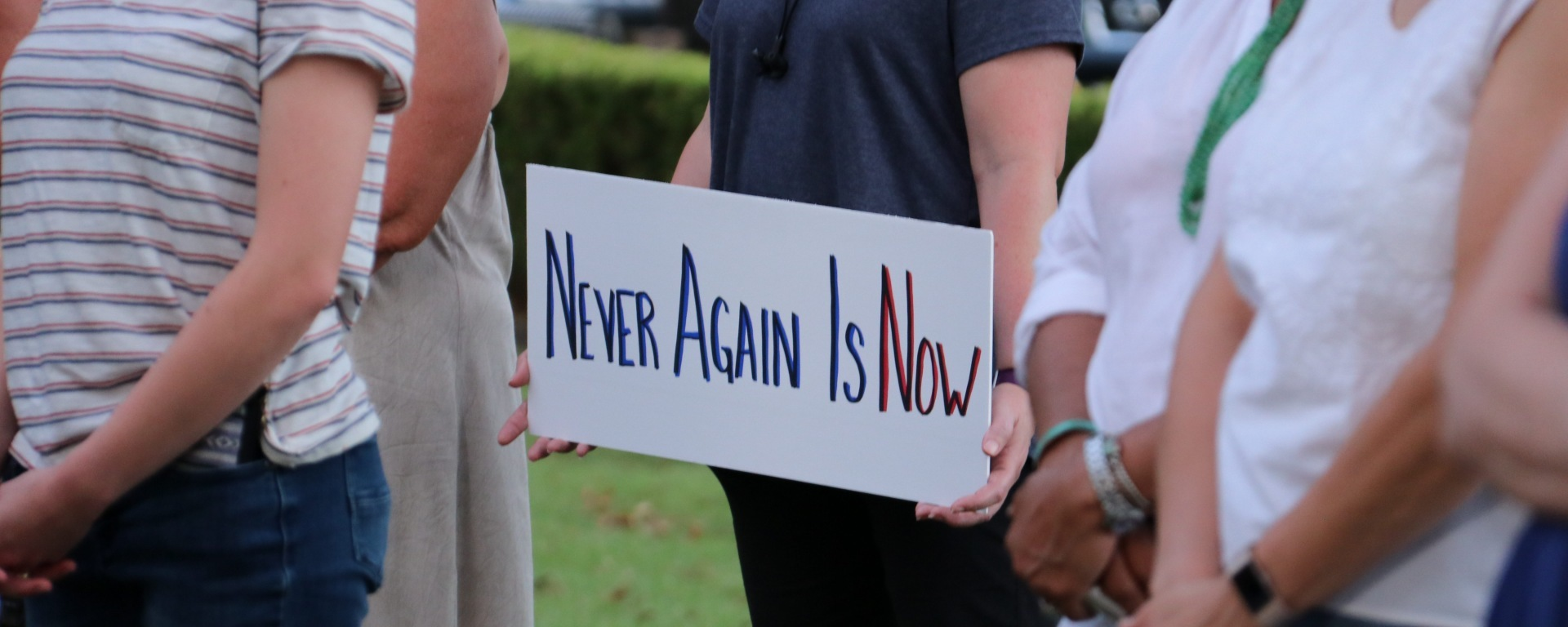 "A lady in a blue shirt holds a sign saying ""never again is now."""