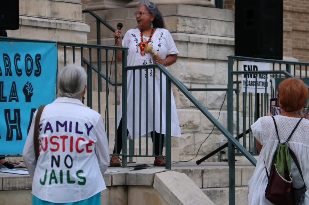 "A senior woman wearing a shirt that reads ""Family, justice, no jails"" looks upon a Native American woman on stage speaking into a microphone and shaking a traditional instrument."