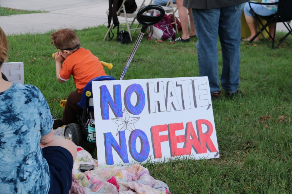 "A young child watches from the lawn of the courthouse as a sign reading ""no hate no fear"" leans on his tricycle."