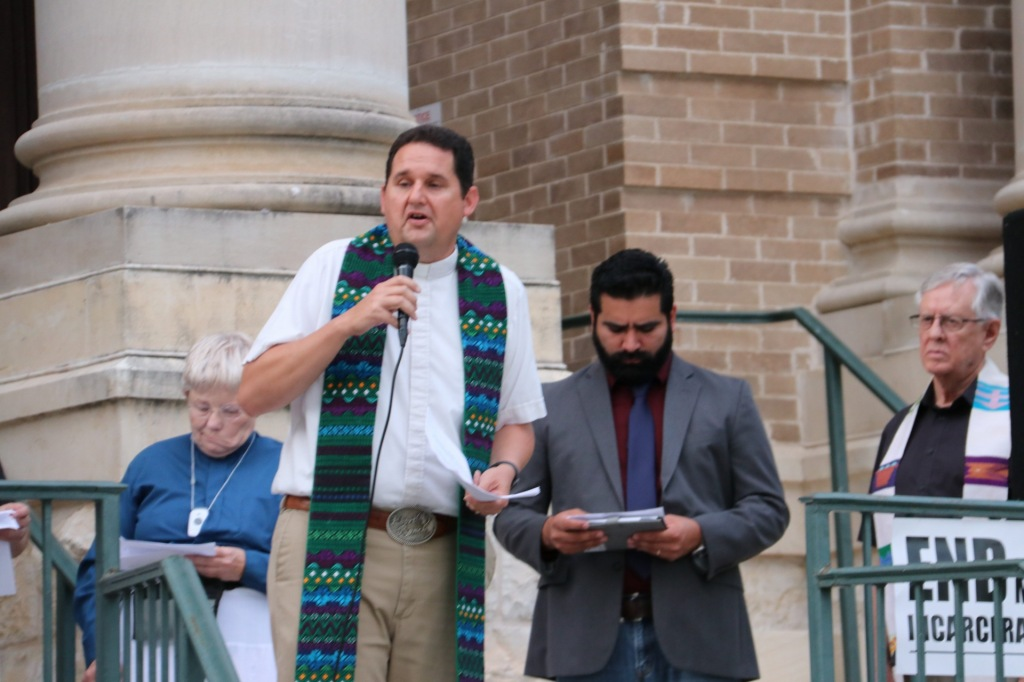 A tall man with a patterned scarf reads from a small sheet of paper into a microphone.
